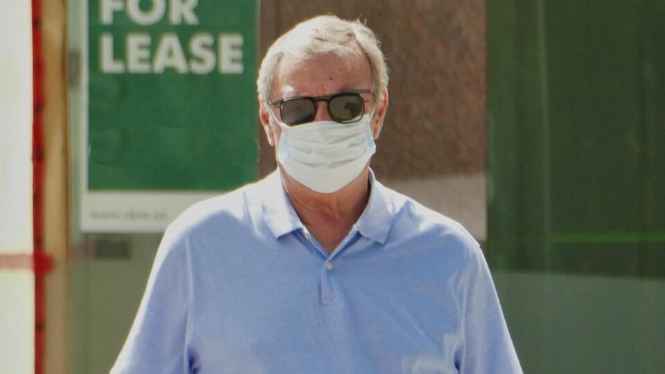 Un homme portant un masque et des lunettes fumées dans une rue de Regina.