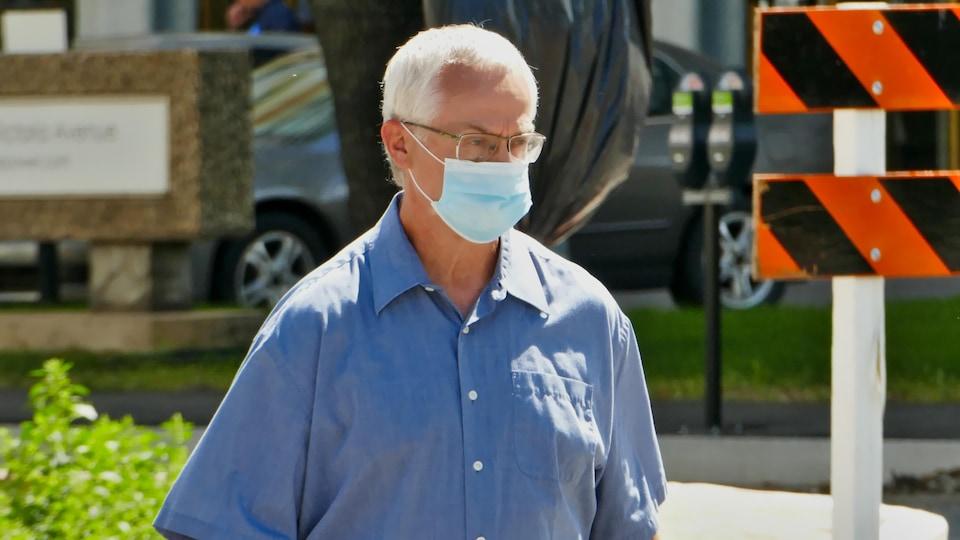 Un homme porte un masque à l'extérieur pendant la pandémie de la COVID-19 à Regina en l'été.