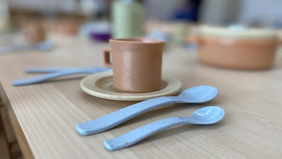 Des ustensiles et une tasse sur une table en bois.