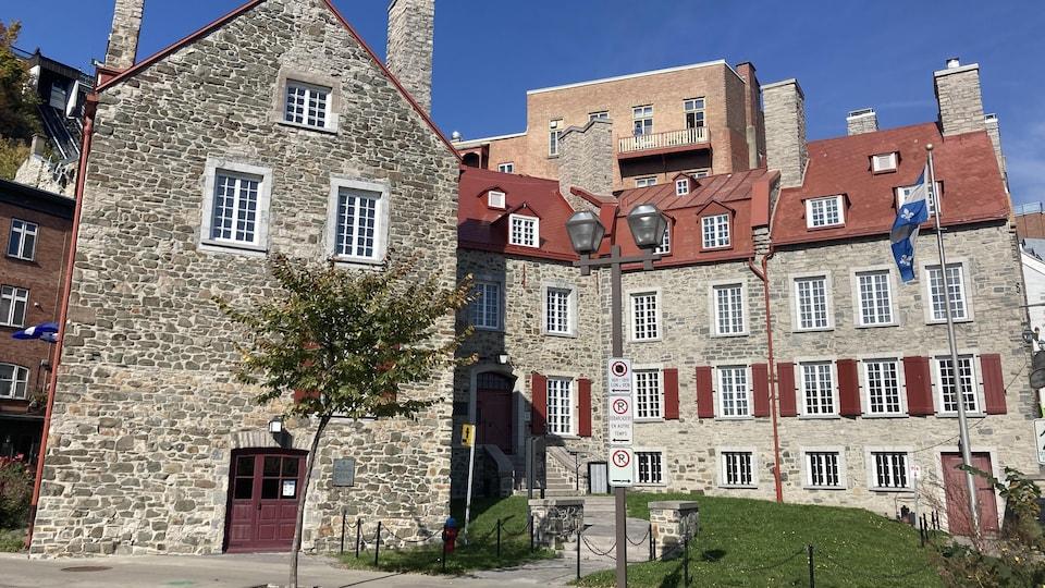 Un bâtiment de pierres à la toiture rouge sang de boeuf