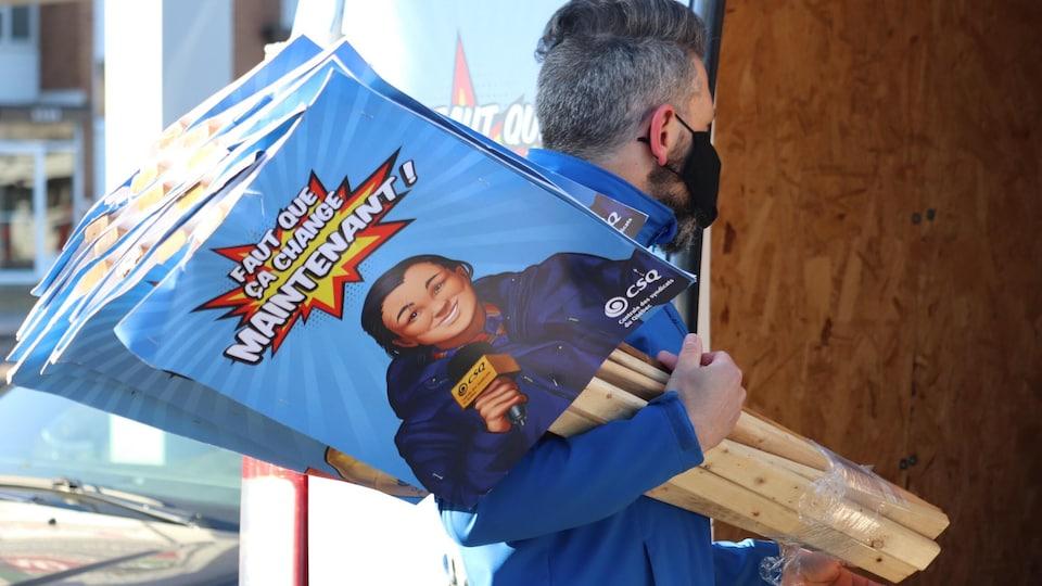 Une personne tient dans ses mains plusieurs pancartes.