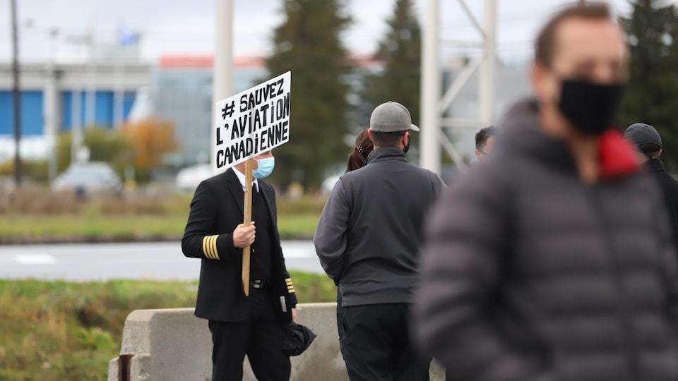 Un manifestant avec une pancarte sur le terrain de l'aéroport de Québec.