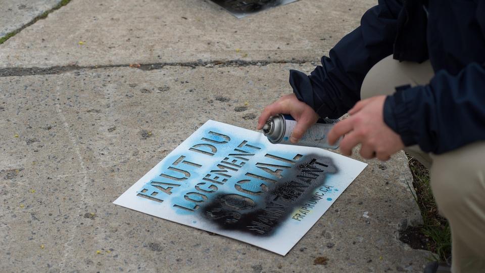 Un manifestant utilise de la peinture en aérosol et un pochoir pour tracer le message « Faut du logement social maintenant ».