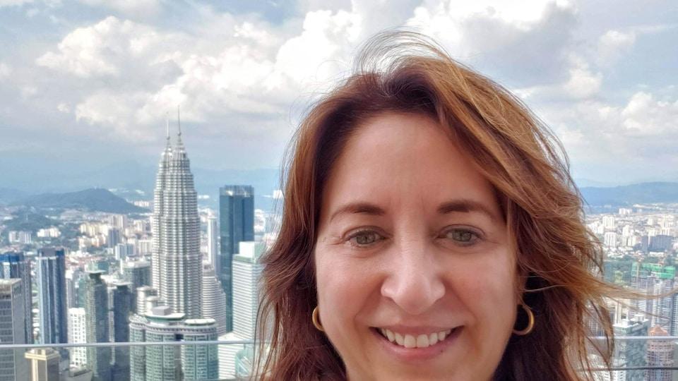 Mireille Robichaud devant des gratte-ciels en Malaisie.