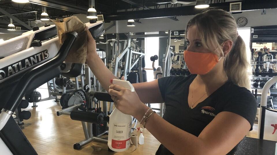 Une femme nettoie l'équipement d'entraînement.