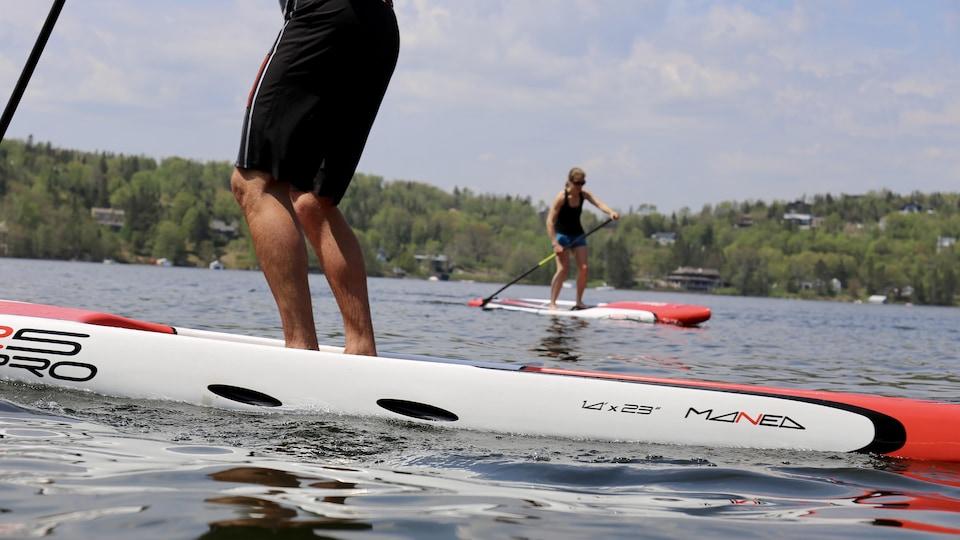Deux personnes font de la planche à pagaie sur un lac.