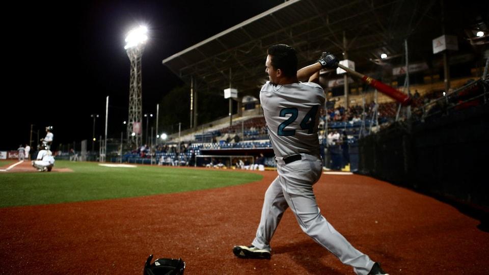 Un joueur de baseball dans un stade la nuit.