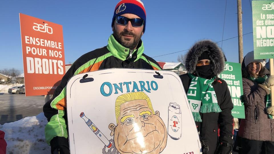 Un homme pose avec une pancarte où l'on peut voir une caricature de Doug Ford.