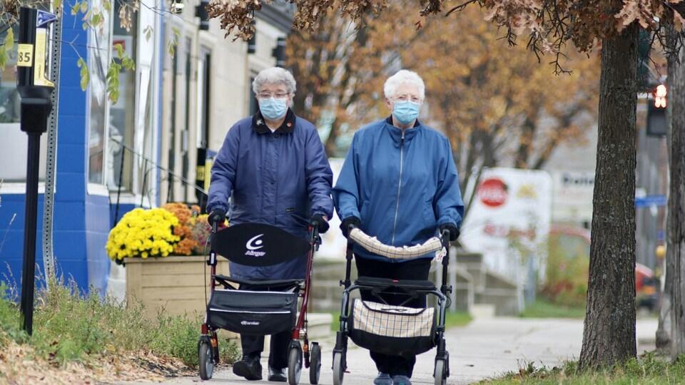 Deux personnes aînés portant un masque marchent sur le trottoir.