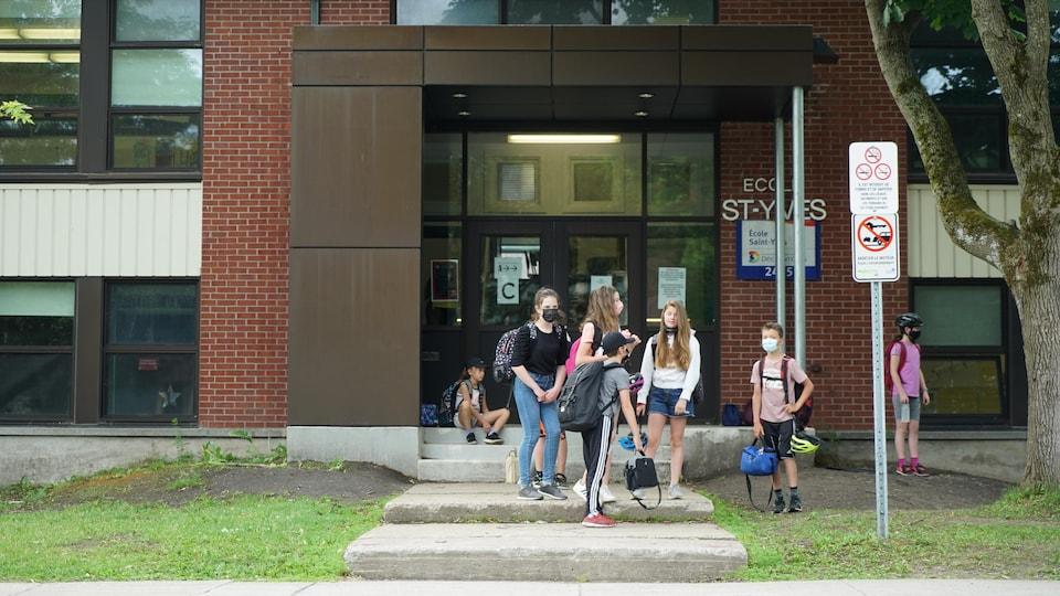Des écoliers devant une école.