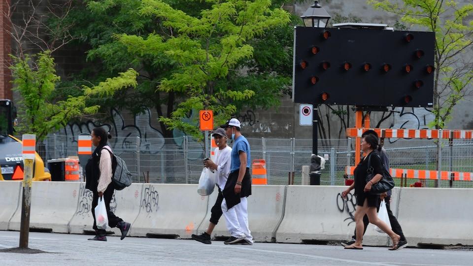 Des personnes marchent dans la rue devant des travaux.