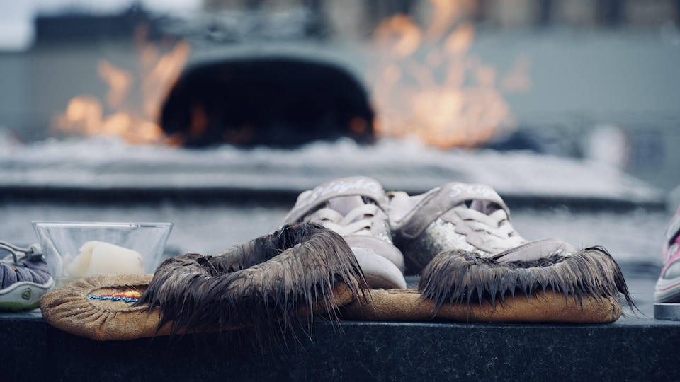 Une paire de mocassins devant la flamme du Centenaire.