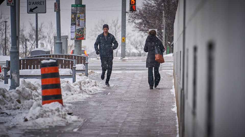Un homme fait son jogging au centre-ville d'Ottawa sous de légers flocons.