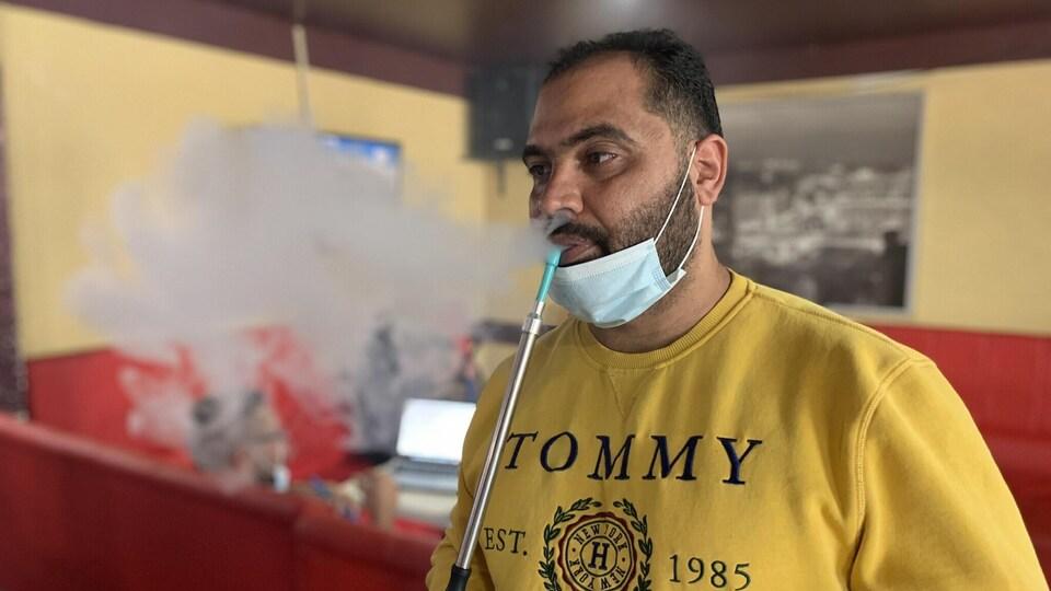 Homme qui fume une pipe à eau.
