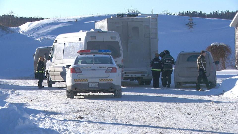 Des véhicules de police et des policiers, l'hiver.