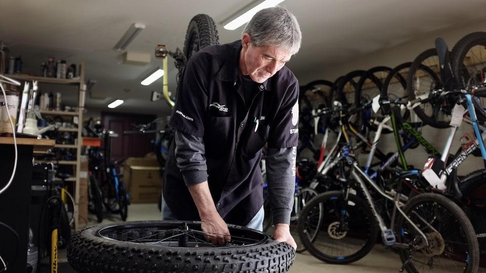 Un homme qui installe un pneu de vélo dans un magasin de vélo.