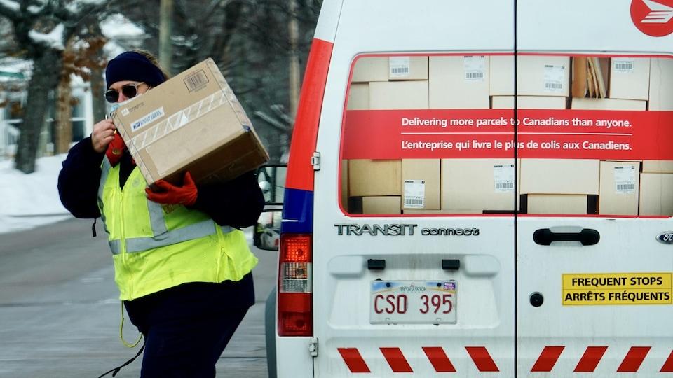 Une travailleuse de Postes Canada s'éloigne de son camion avec un colis, le 14 janvier 2021 au Nouveau-Brunswick.