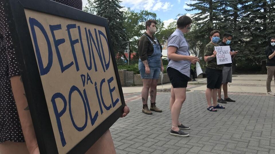Gros plan sur une pancarte où il est demandé de diminuer les fonds versés à la police.