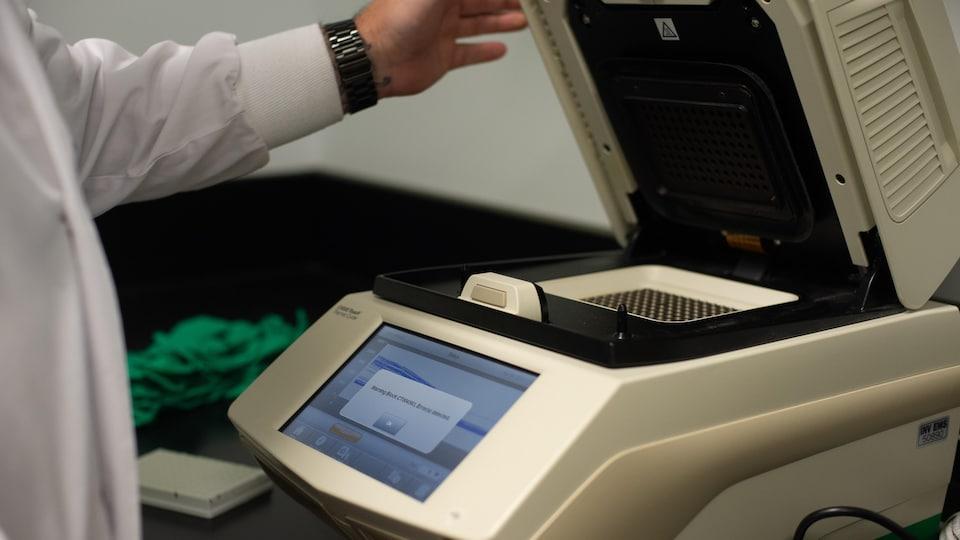 Une main ouvre le couvercle d'un appareil muni d'un écran.
