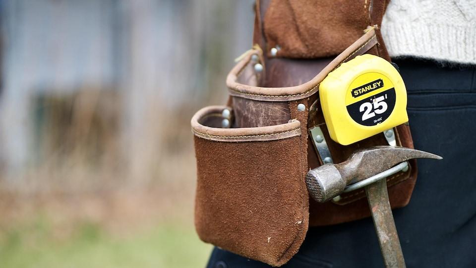 Des outils à la ceinture d'un ouvrier.