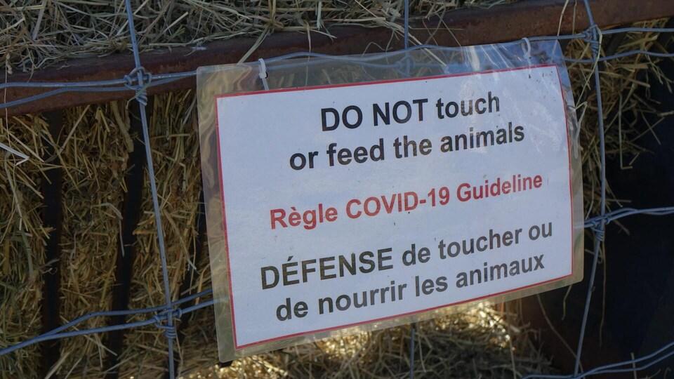 Une affiche qui mentionne : « Règle COVID-19 : Défense de toucher ou de nourrir les animaux » en anglais et en français.