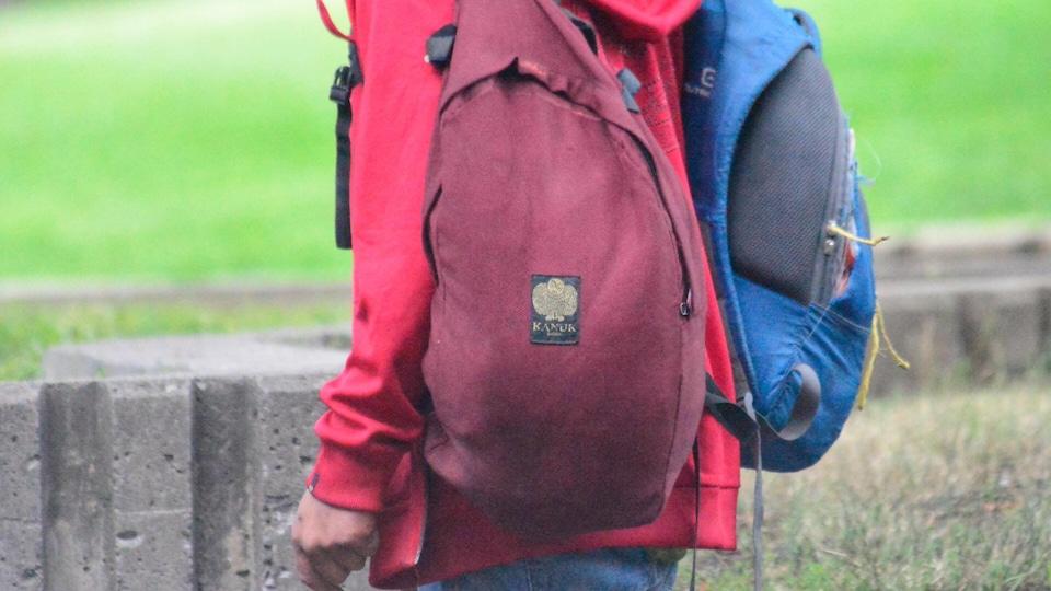 Sans-abri marchant avec deux sacs à dos troués