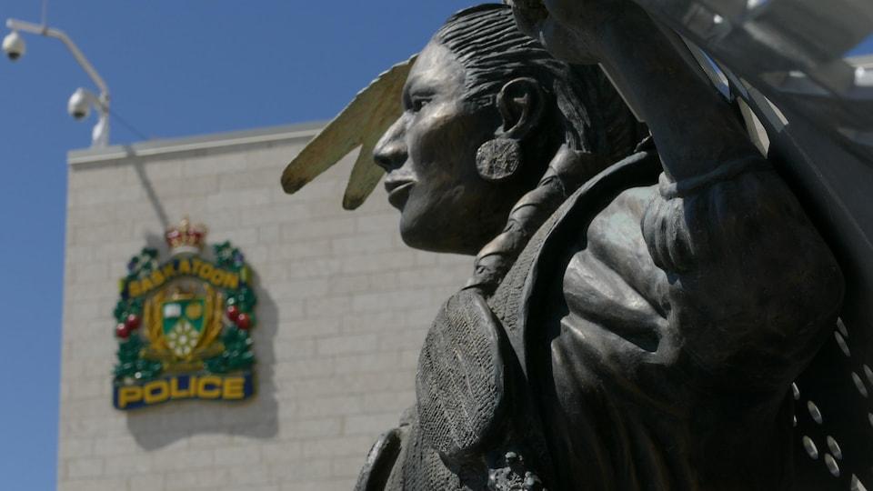 Une sculpture représentant une personne autochtone devant la station de police de Saskatoon.