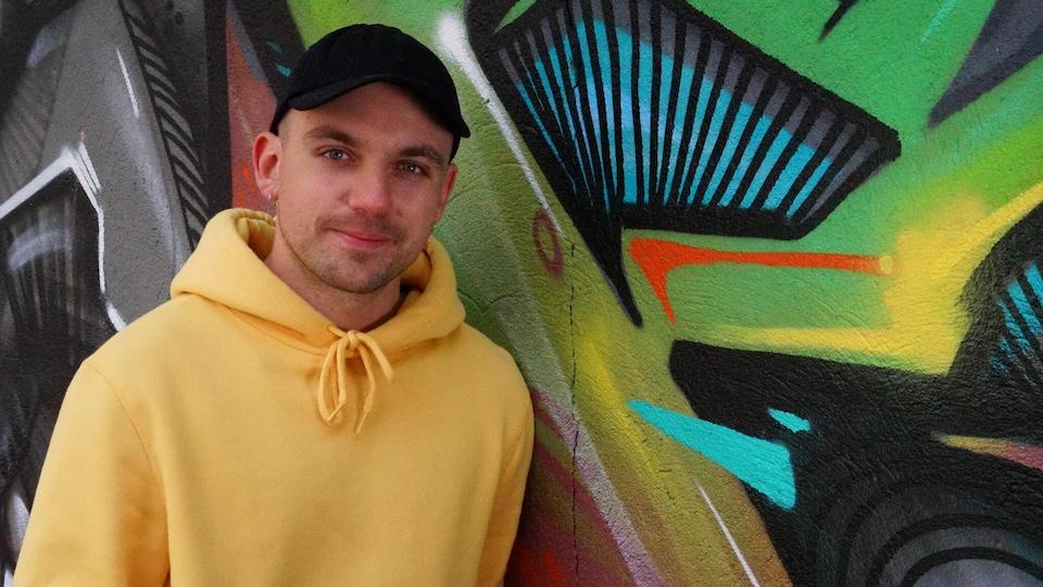 Le musicien fransaskois Shawn Jobin devant une murale à Saskatoon.