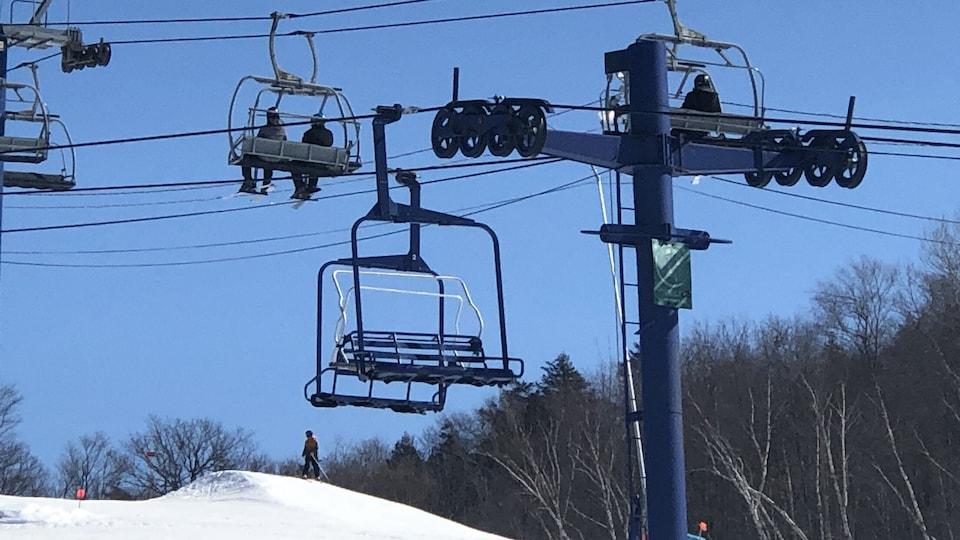 Deux skieurs sont sur une remontée mécanique de station de ski.