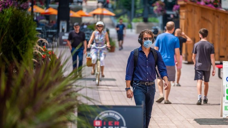 La rue Sparks à Ottawa, en été, avec des passants masqués.