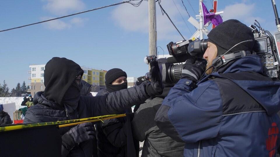 Des gens aux bords de la barricade de Saint-Lambert