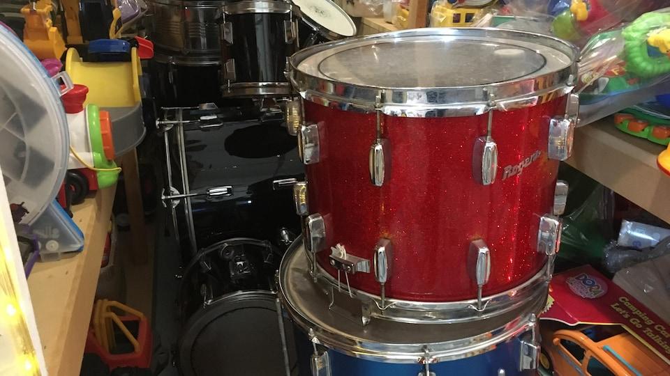 Des tambours sont empilés sur le sol de l'entrepôt.