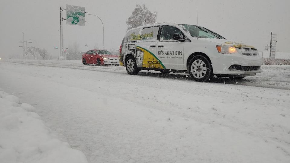 Une voiture passe sur une rue enneigée de Gatineau.