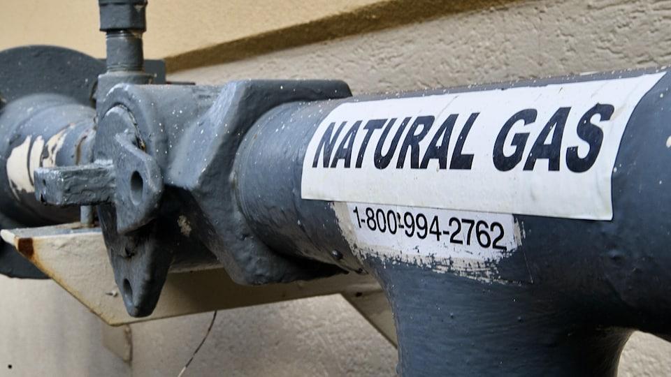 Une canalisation sur laquelle est apposée un autocollant où l'on peut lire, en anglais, gaz naturel.