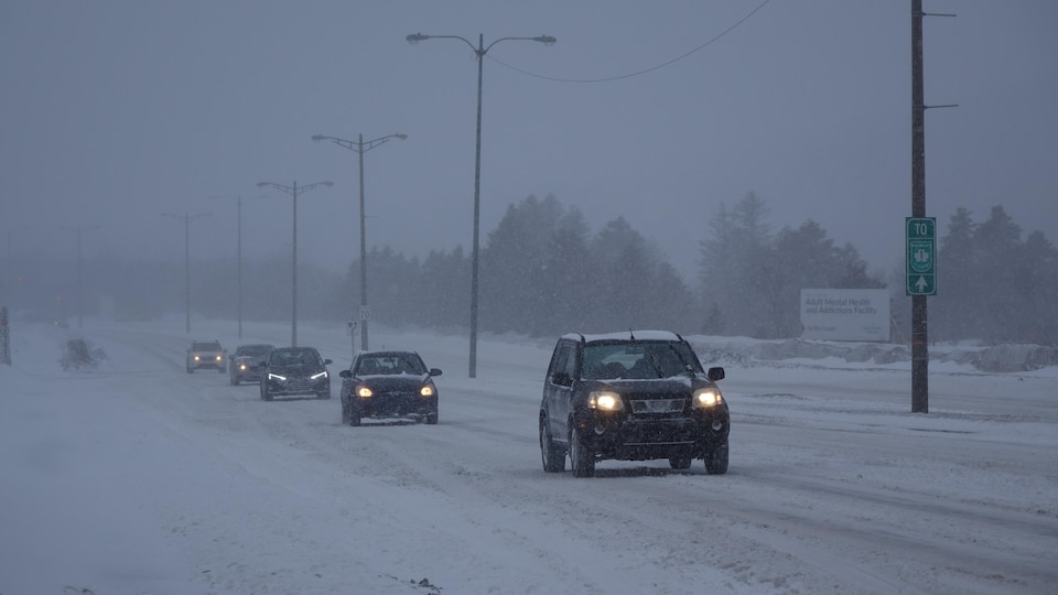 Des voitures circulent sur une route enneigée.