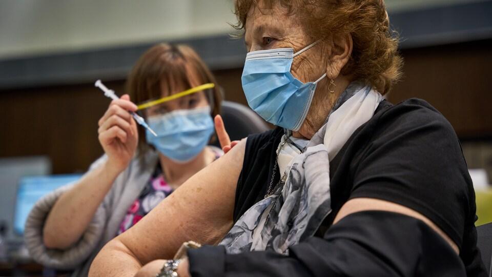Une femme tient une seringue près du bras d'une aînée.
