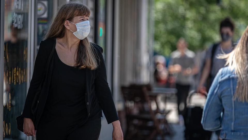 Une femme portant le masque marche sur le trottoir.