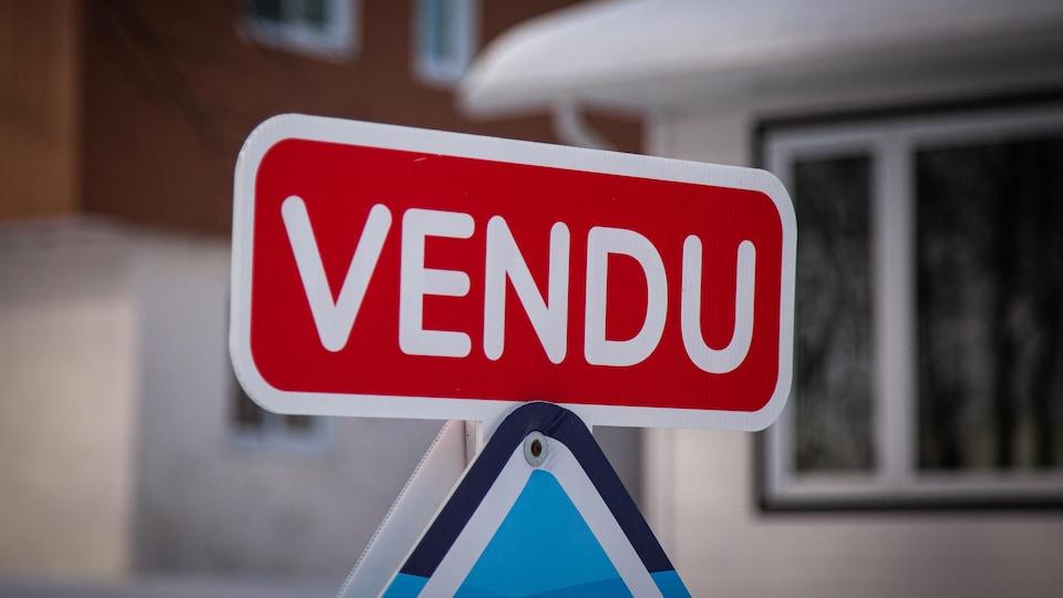 Carton « vendu » installé sur une affiche de courtier immobilier.