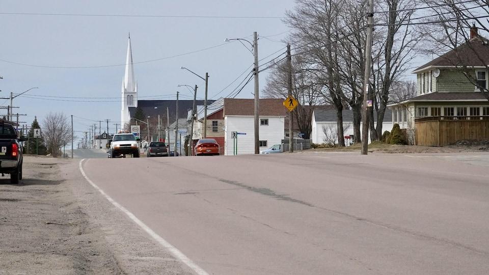 Une rue du village et le clocher de l'église dans le lointain.