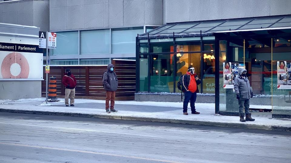 Des personnes attendent l'autobus en maintenant la distanciation physique et en portant le masque.