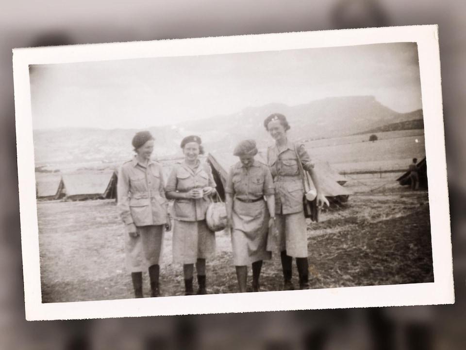 Cette photographie illustre quatre femmes en habits militaires au campement. La deuxième à gauche et la dernière ont leurs sacs à main. La deuxième à gauche a aussi une tasse dans les mains alors que la dernière à droite a une cigarette. Au deuxième plan, on observe plusieurs tentes. En arrière-plan, on observe quelques champs et un paysage montagneux. Cette photographie a été prise entre les années 1939 et 1945.