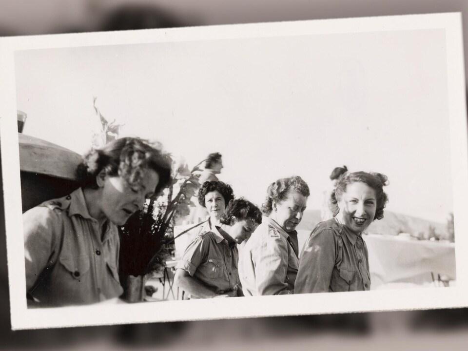 Cette photographie illustre cinq jeunes femmes assises, faisant une opération annuelle. On note que deux de ces jeunes femmes regardent l'objectif. On observe un bouquet de fleurs près des femmes. En arrière-plan, on observe une table nappée et une personne qui marche. Cette photographie a été prise entre les années 1939 et 1945.