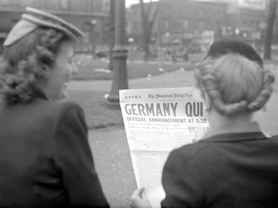 Deux jeunes femmes, debout, rue Sainte-Catherine à Montréal, lisent la une du journal The Montreal Daily Star. Ce titre annonce la capitulation allemande et la fin imminente de la Seconde Guerre mondiale.