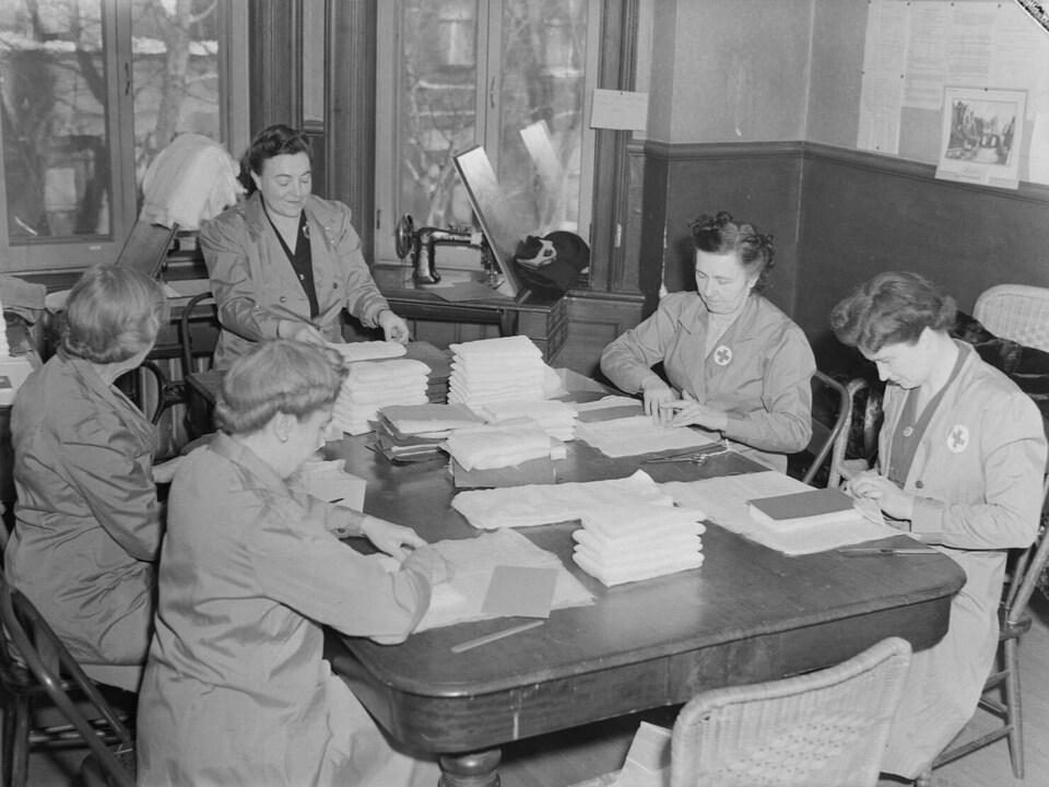 Des femmes bénévoles, portant des sarraus de la Croix-Rouge, préparent des pansements de gaze dans un local de la Croix-Rouge situé à Westmount.