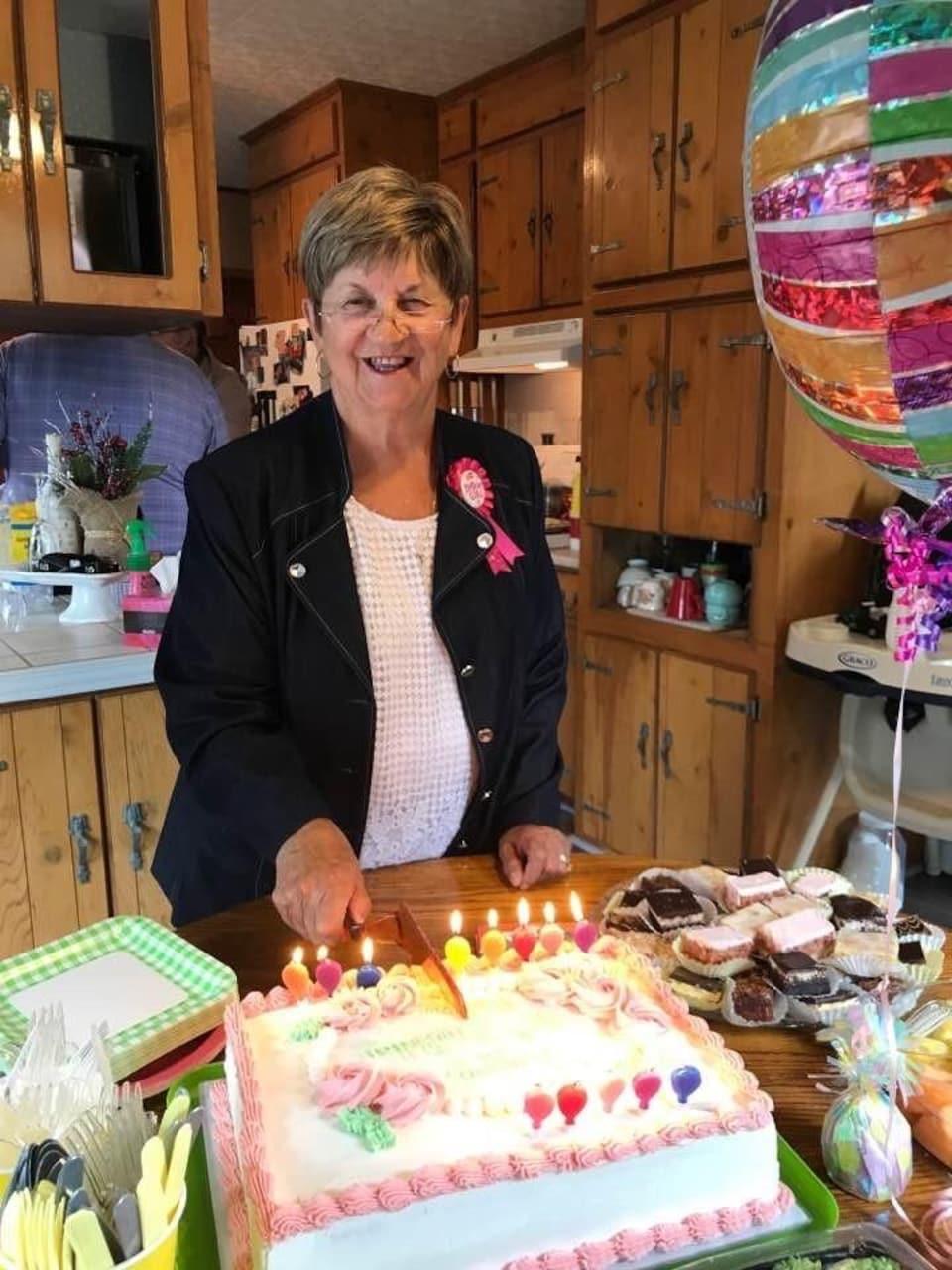 Pauline D'Entremont coupe un gâteau d'anniversaire.
