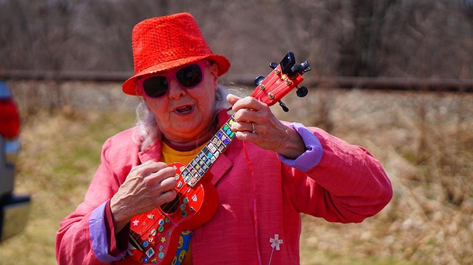 Une femme joue du ukulele.