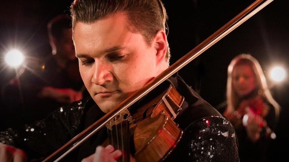 Gros plan sur le visage d'un jeune homme jouant du violon.
