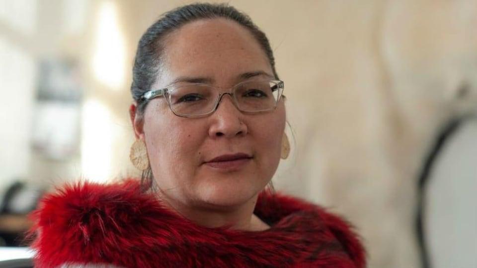Aluki Kotierk, une dame, porte des lunettes et un chandail rouge.