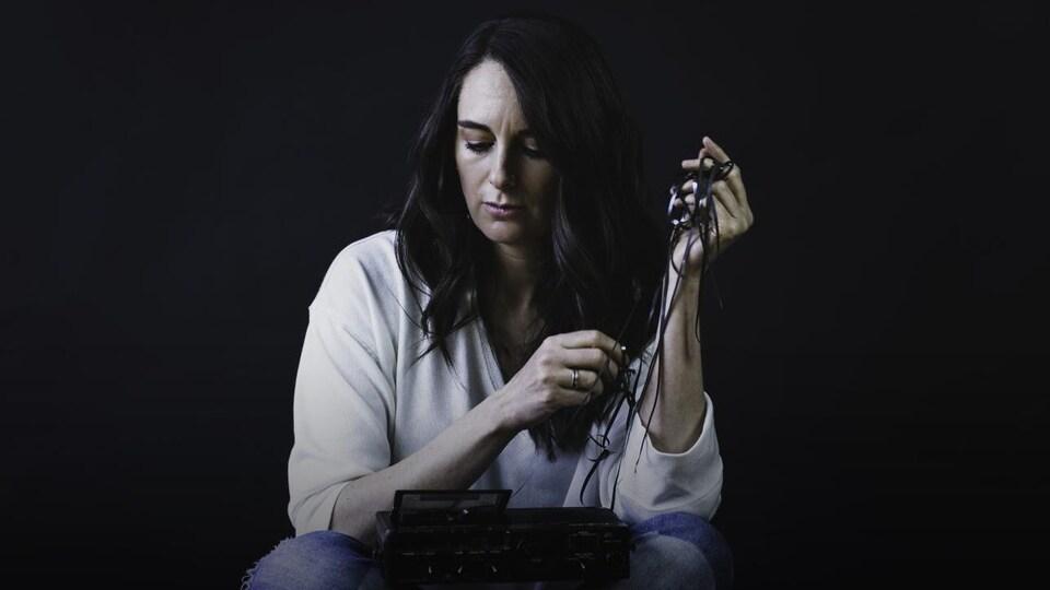 Anique Granger, chandail blanc et jeans, a un magnétophone à cassette entre les genoux. Elle tire sur le ruban de la cassette.