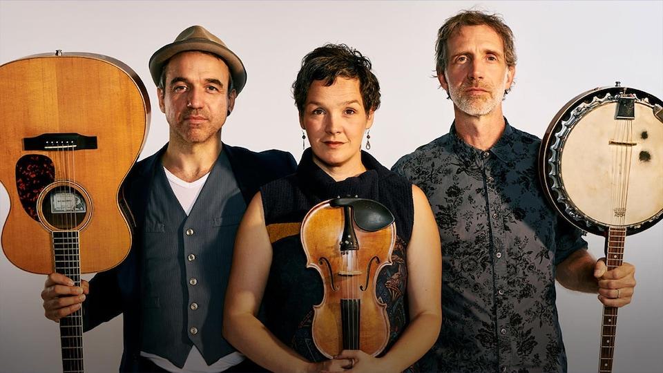 Dominic Desrochers, Jean- François Dumas et Véronique Plasse, de la formation Bon débarras, tenant leur instrument (guitare, violon et banjo) à l'envers.